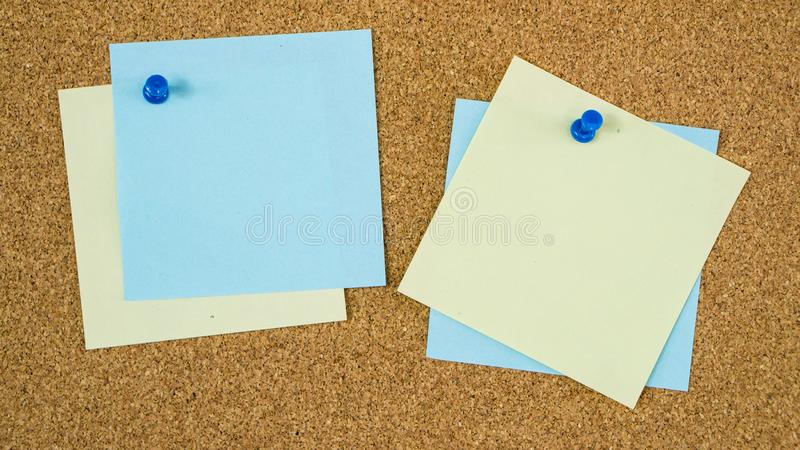 Different color post it notes pinned on cork board stock photo