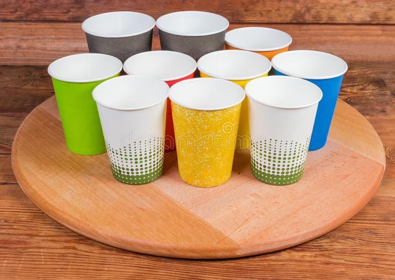 Different empty disposable paper cups on the wooden serving board. Empty disposable paper cups different sizes and colors on the round wooden serving board on stock photography
