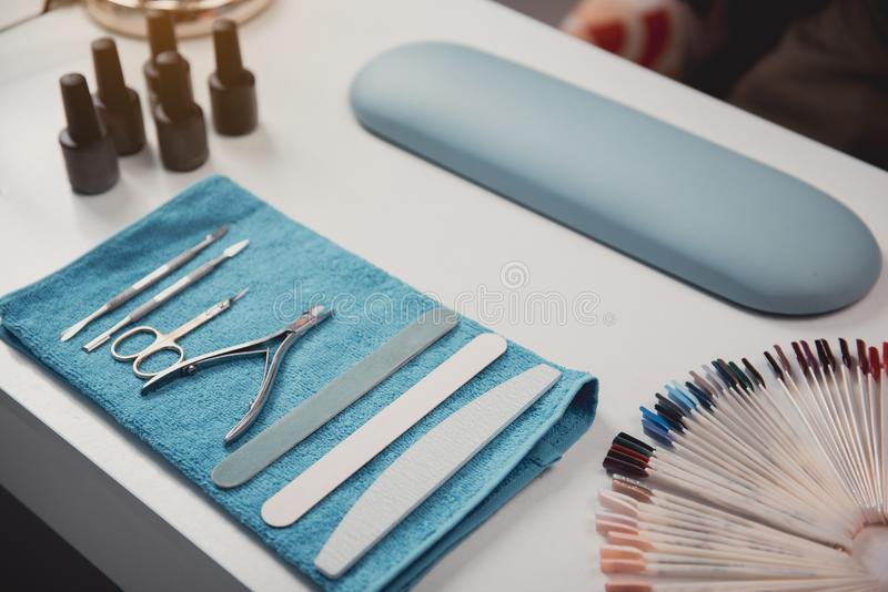 Tools for preparing manicure on table. Different equipment for creating manicure situating on desk in beauty salon. Glamour and work concept. Close up royalty free stock photography