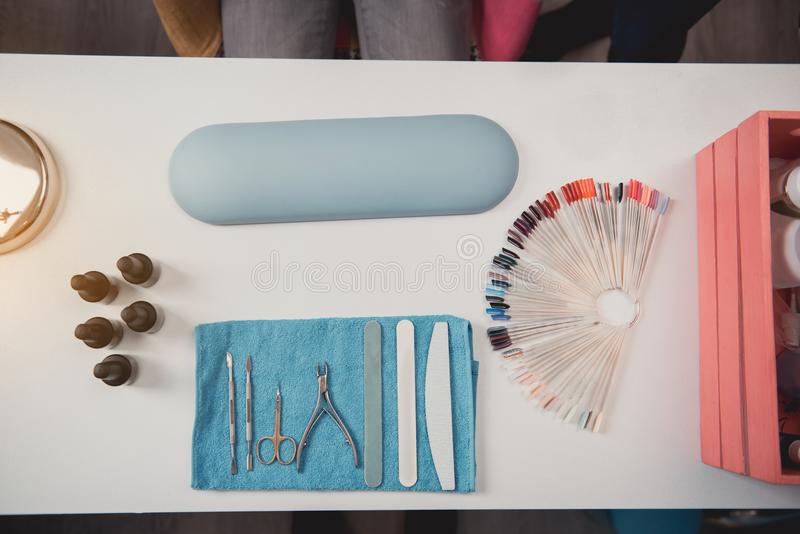 Different equipment for creating manicure. Top view nail file, nail buffer, clippers and emery board with examples of nail polish locating on table in beauty royalty free stock photography