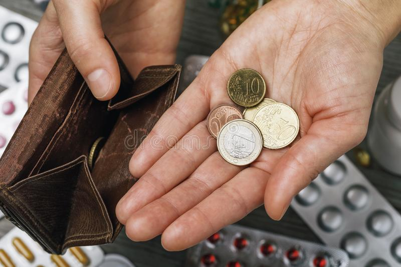 Different euro coins in hand with empty wallet on pill background. Concept on the lack of money to buy drugs royalty free stock image