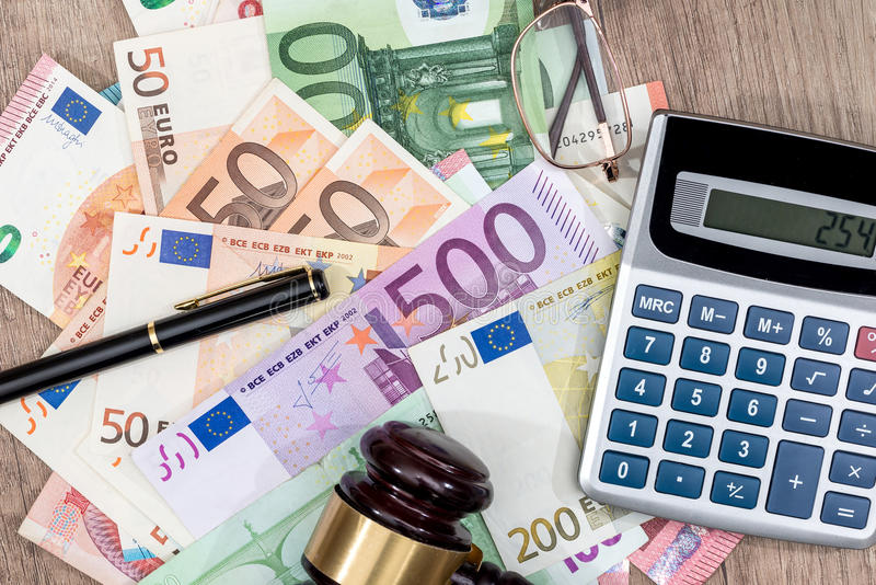 Different euros bills, hammer, calculator and pen. On desk royalty free stock photography