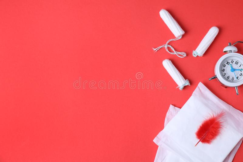 Different feminine hygiene products, alarm clock and red feather on color background, flat lay. Gynecological. Different feminine hygiene products, alarm clock stock images
