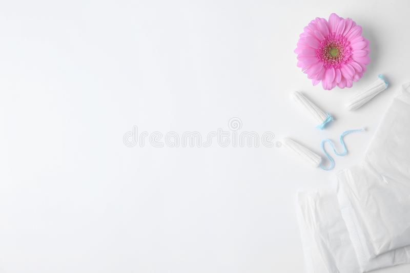 Different feminine hygiene products and flower on white background, top view with space for text. Gynecological care royalty free stock photos