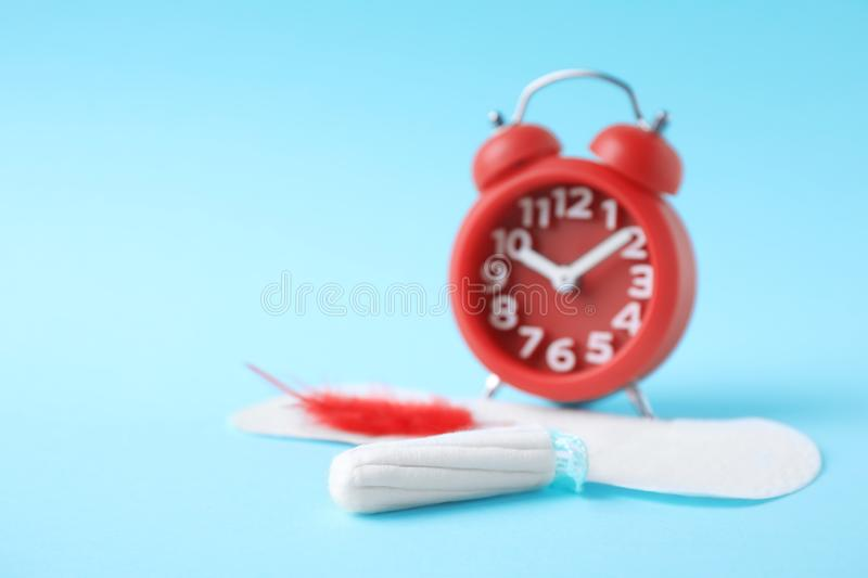 Different feminine hygiene products with red feather and alarm clock on color background. Gynecological care. Different feminine hygiene products with red stock photos