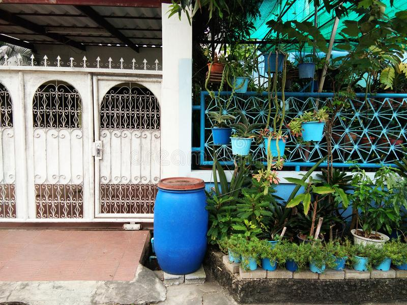 Different fence between two houses. Blue bin in front of pole in between different fence of two houses royalty free stock images