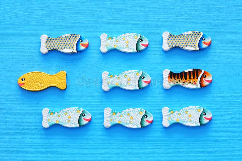 Different fish swimming opposite way of identical ones. Courage and success concept. Different fish swimming opposite way of identical ones. Courage and success stock images