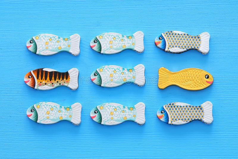 Different fish swimming opposite way of identical ones. Courage and success concept. Different fish swimming opposite way of identical ones. Courage and success stock photo