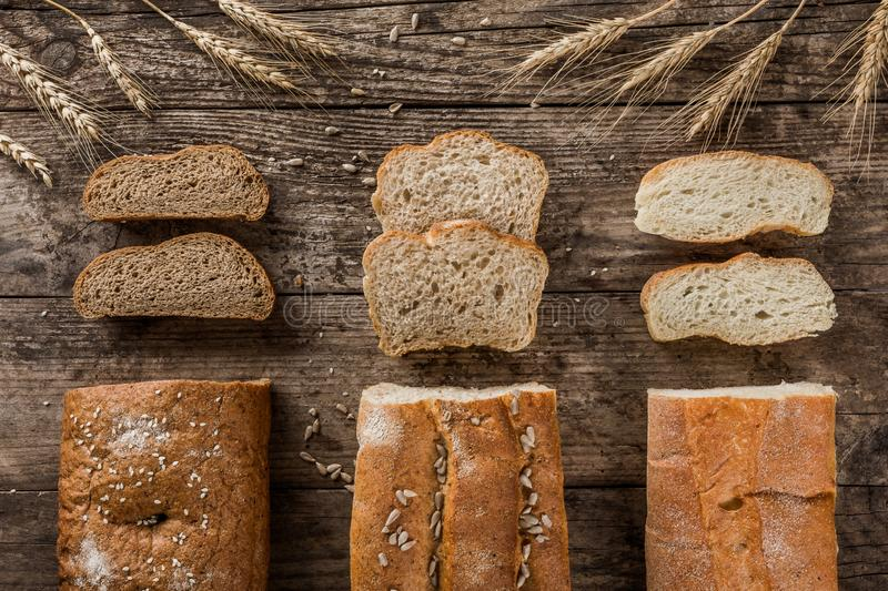Different fresh bread and spikelets of wheat on rustic wooden background. Creative layout made of bread. stock images