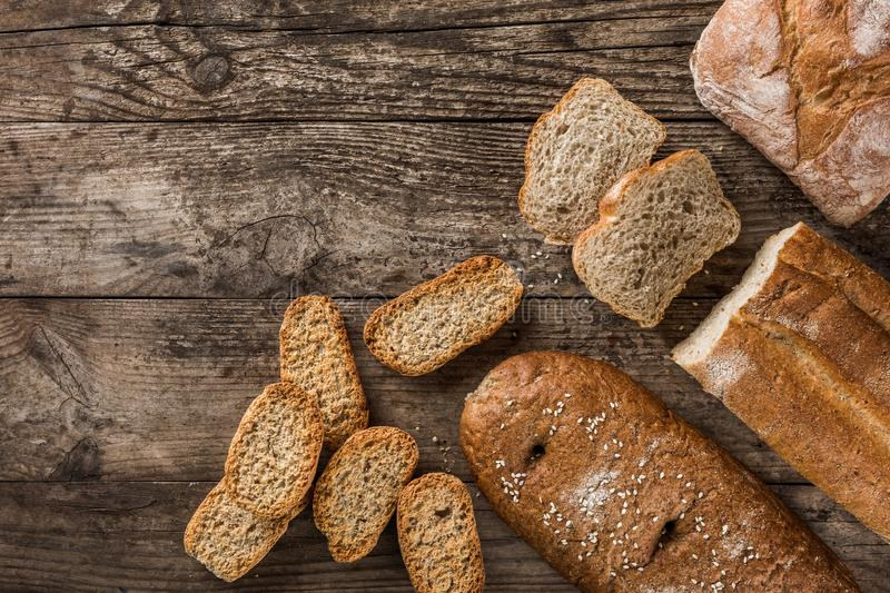 Different fresh bread and spikelets of wheat on rustic wooden background. Creative layout made of bread. Healthy food concept, top view, flat lay, copy space stock images