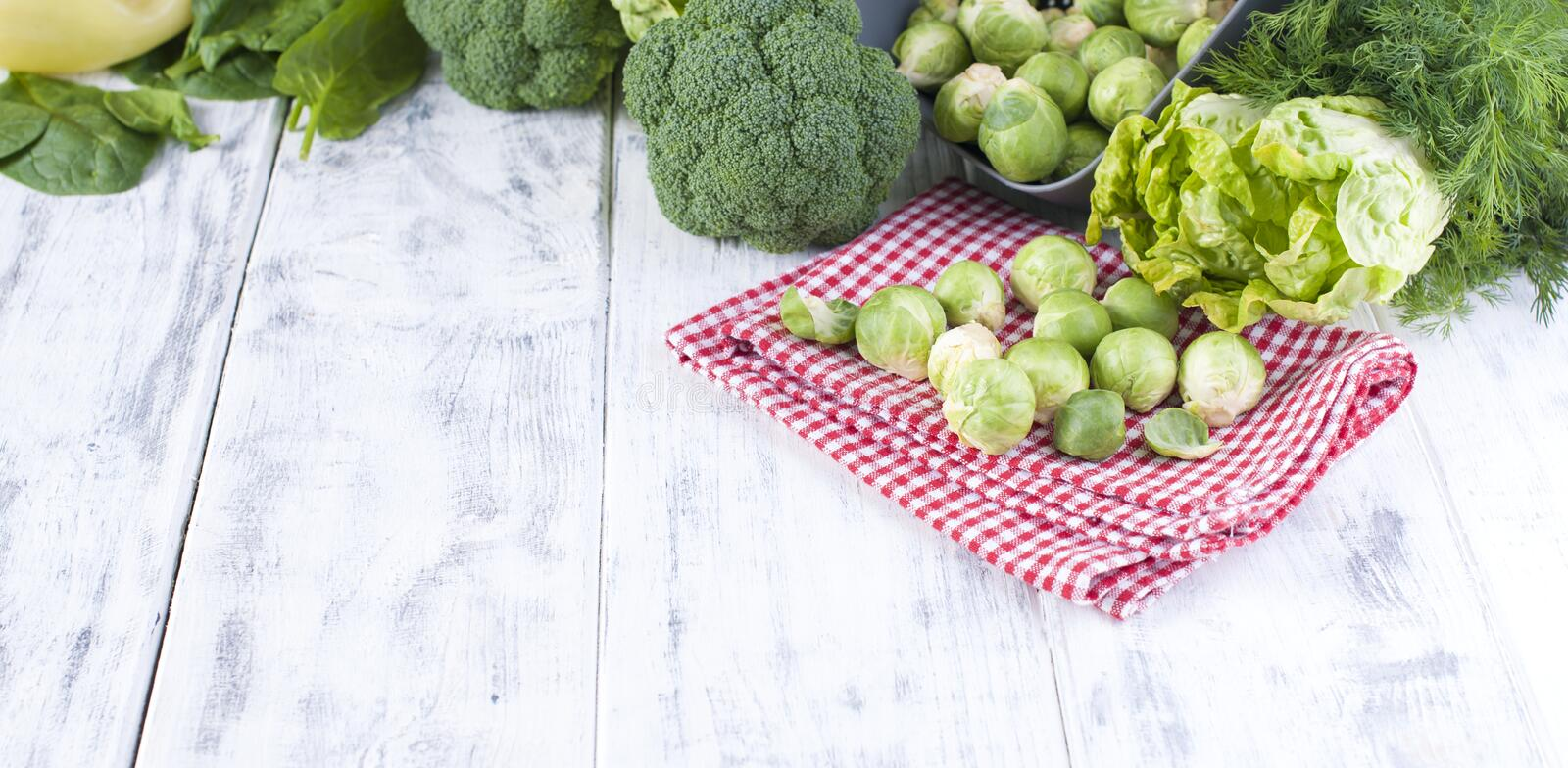 Different fresh green vegetables, brussels sprouts and vegetables. On a white wooden background. place of writing text. stock images