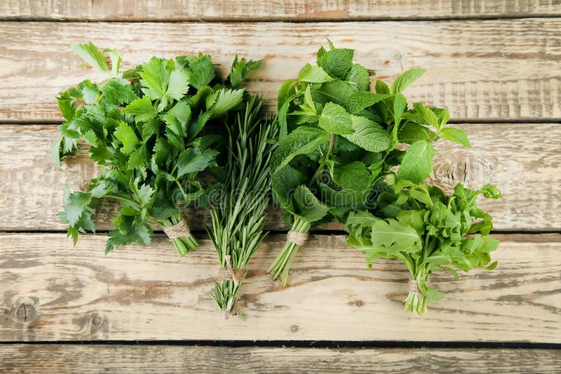 Different fresh herbs. On brown wooden table stock photos