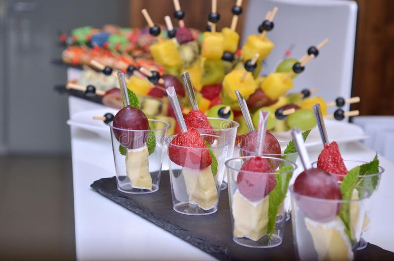 Different fruit and cheese canapes in transparent glasses and wooden skewers on a glass step support on a table royalty free stock photo