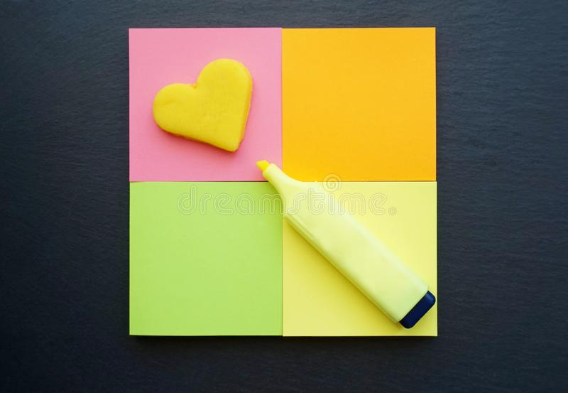 School supplies in vivid color, sticky notes and marker pen flat lay on the black board background royalty free stock photos
