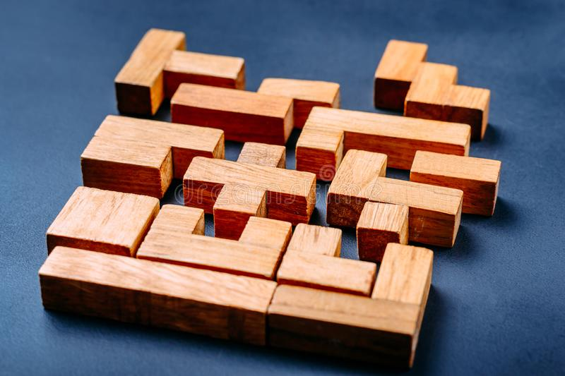 Different geometric shapes wooden blocks on a dark background. Creative, logical thinking and problem solving concept stock photo