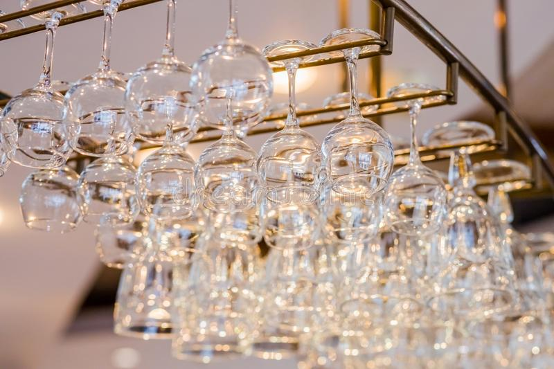 Different glasses hanging over the bar.selective focus.horizontal low angle image of glasses stacked on metal hanging royalty free stock images