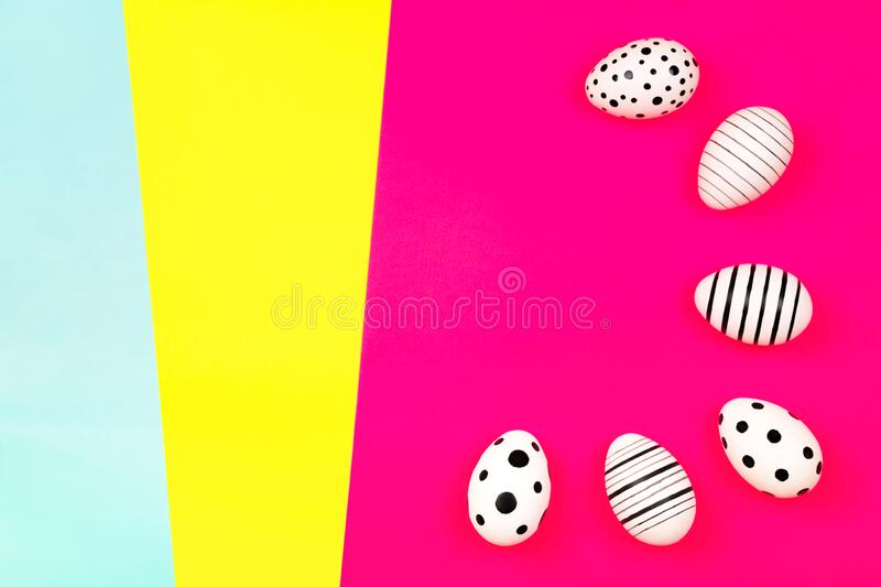 Different graphic hand-painted eggs on bright pink background. Easter concept. Place for text royalty free stock images