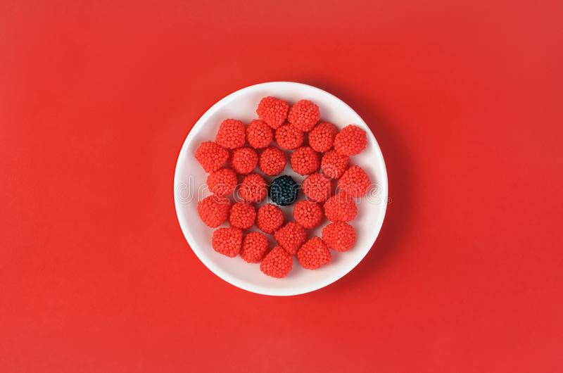 Different gum sweets in the form of fruit berries on red royalty free stock photography