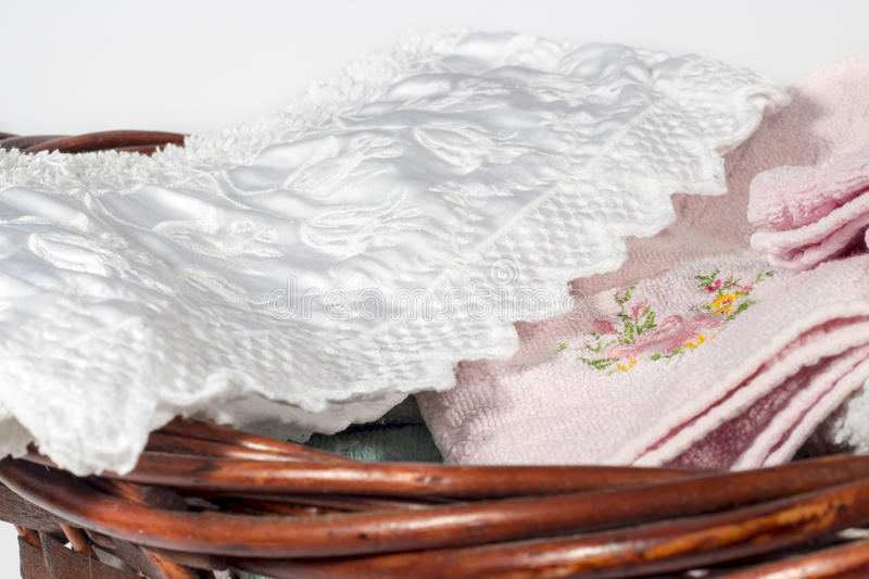 Different hand towels into a wicker basket, on white background. Wicker basket for bathroom containing several hand towels of different colors and patterns. On stock images