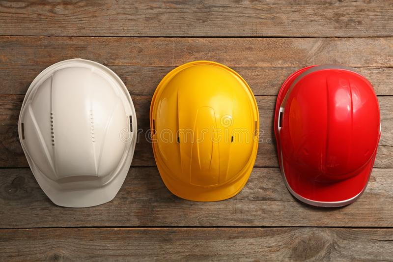 Different hard hats on wooden background, top view. stock photos