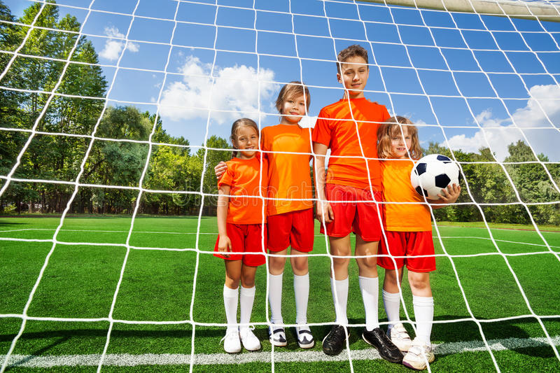 Different height kids stand in line with football stock photos