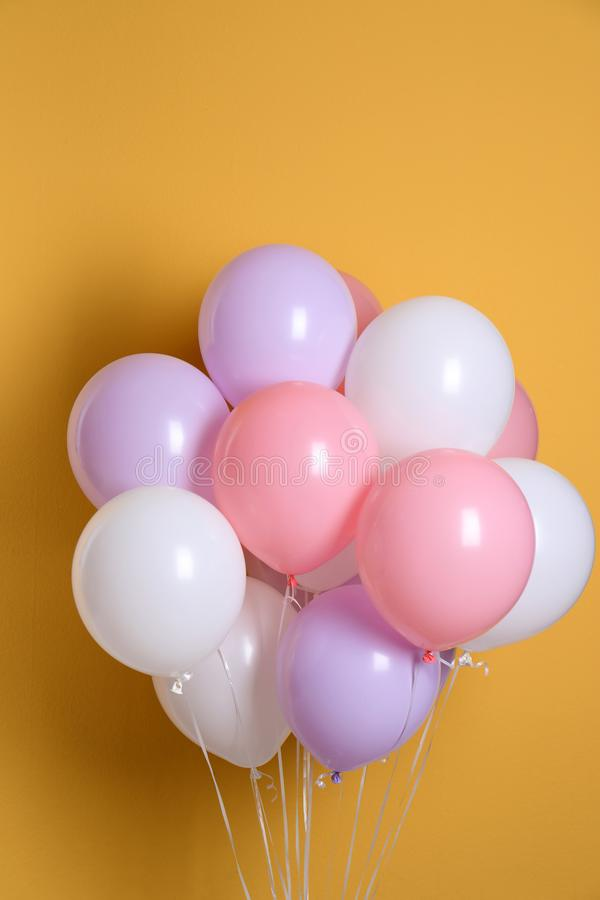 Different helium party balloons. On color background stock photography