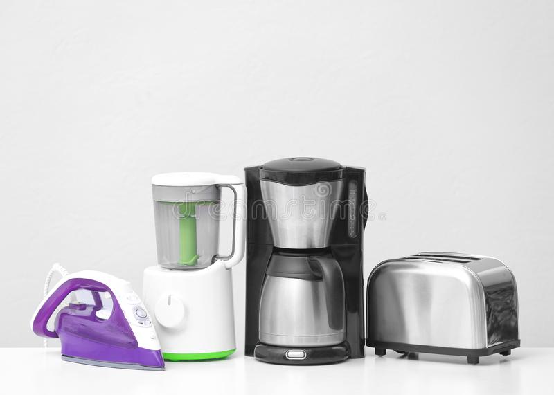 Different household and kitchen appliances on table against light background. Interior element royalty free stock images