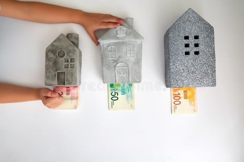Different houses and price in Israeli currency. From above creative composition of small and bigger houses with different price in Israeli new shekel royalty free stock photo
