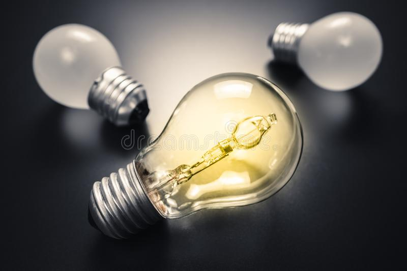 Different Idea Success. Different and bigger light bulb glowing on black background, creative thinking, find your own way royalty free stock photos
