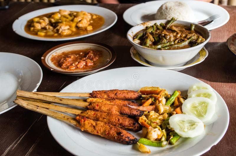 Different Indonesian dishes: Sate Pusut focused foreground, Ikan asam manis, olah-olah, sambal and rice on table.  royalty free stock images