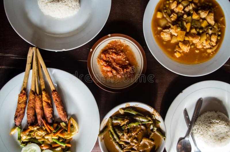 Different Indonesian dishes: Sate Pusut, Ikan asam manis, olah-olah, sambal and rice.  royalty free stock images