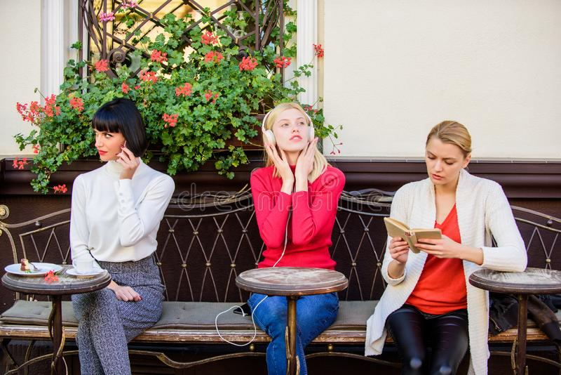 Different interests. Group pretty women cafe terrace entertain themselves with reading speaking and listening. Information source. Female leisure. Weekend stock photo