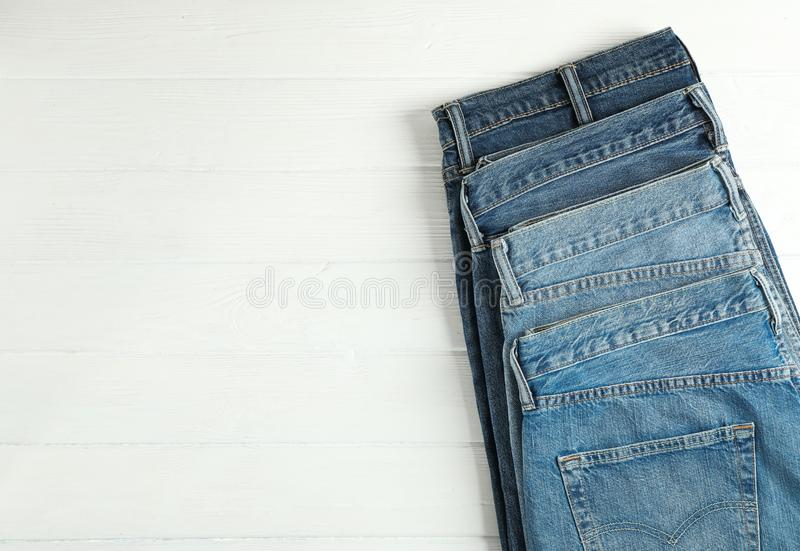Different jeans folded on a white wooden background. Space for text royalty free stock images
