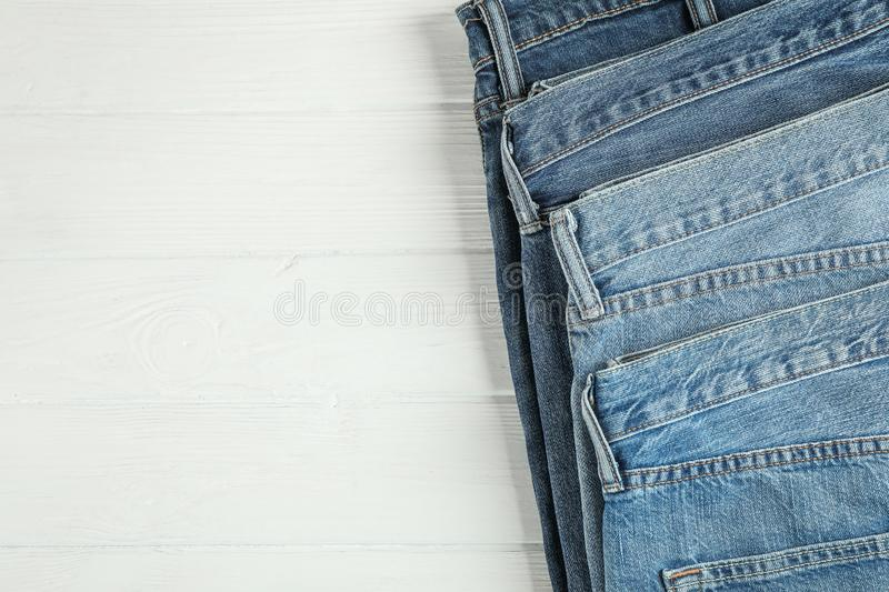 Different jeans folded on a white wooden background. Space for text stock image