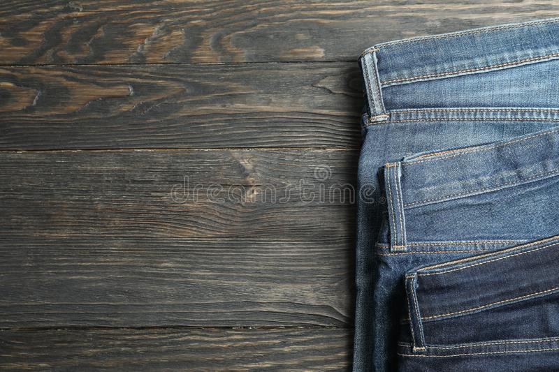 Different jeans folded on a wooden background. Space for text stock image