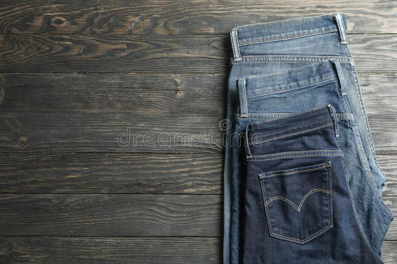 Different jeans folded on a wooden background. Space for text stock photography