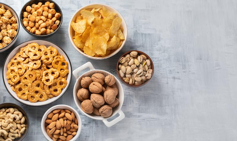 Different kids of snacks, chips, nuts and popcorn stock image
