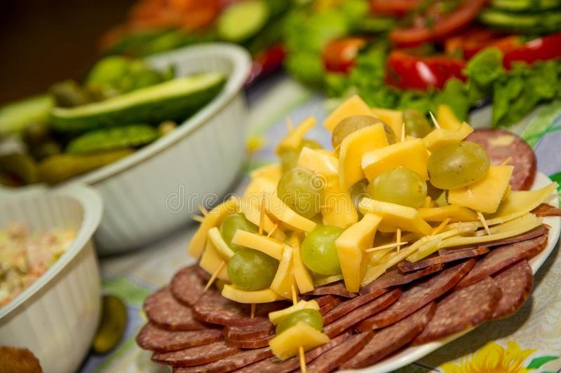 Different kind of sausage and ham are laid out in a plate with cheese and grapes stock photography