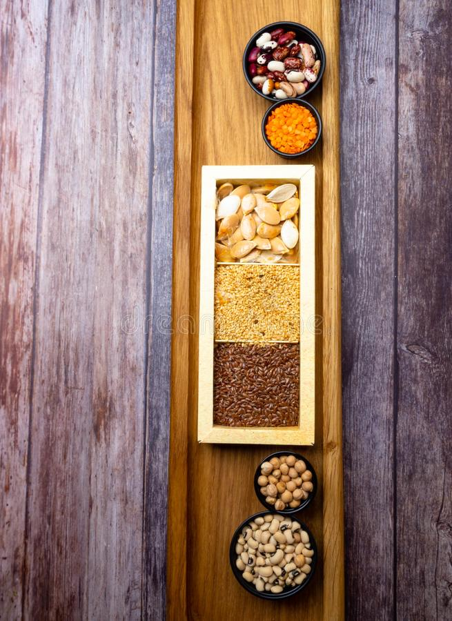 Different kinds of bean seeds, lentil, peas in dish on wooden table, macrobiotic food or healthy food royalty free stock images