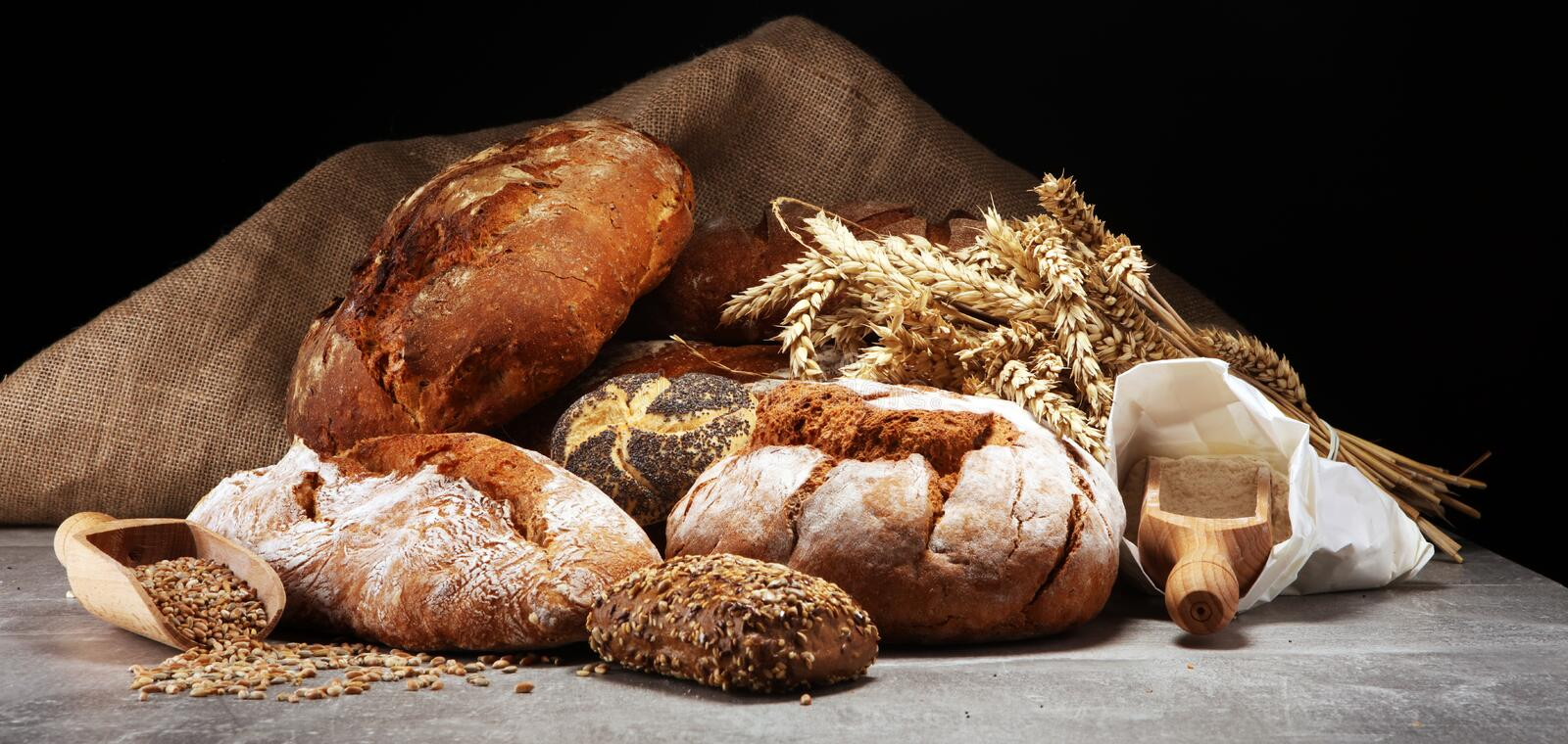 Different kinds of bread and bread rolls on board from above. Kitchen or bakery stock image
