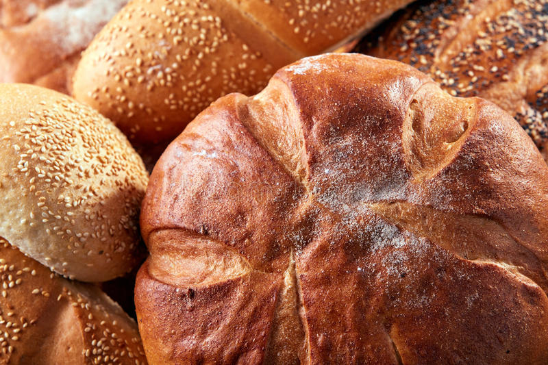 Different kinds of bread and bread rolls on board from above. Kitchen or bakery poster design. Close-up. stock photography