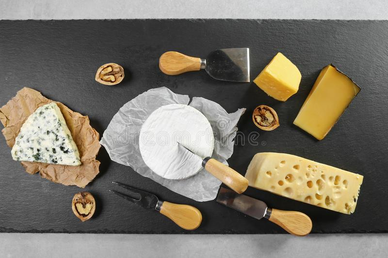 Different kinds of cheeses camembert, brie, parmesan, blue cheese captured from above top view . Black chalkboard as background. L royalty free stock photos