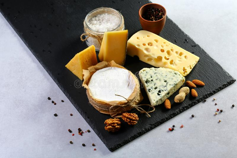 Different kinds of cheeses camembert, brie, parmesan, blue cheese captured from above top view. on a black shale board. Layout wit stock photography