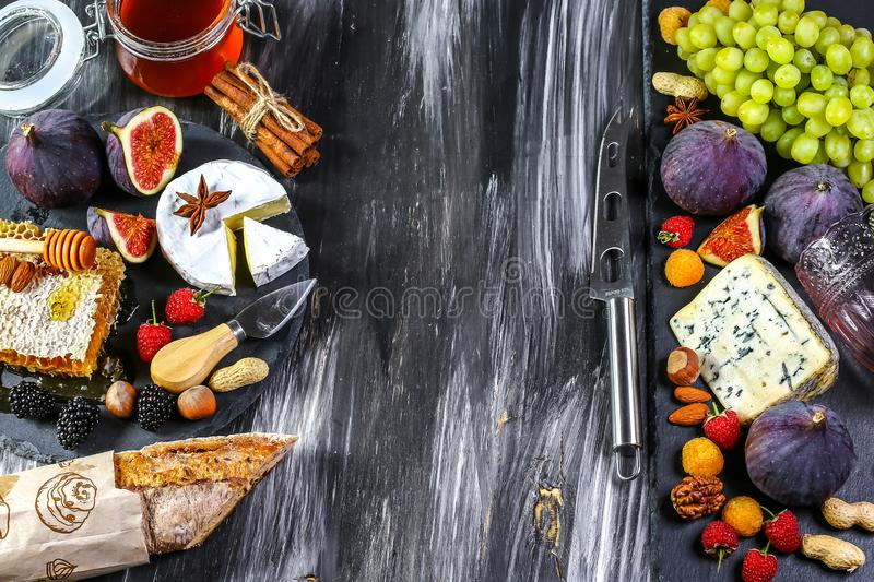 Different kinds of cheeses, wine, baguettes, fruits and snacks on rustic wooden table from above. French tasting party or feast royalty free stock photo