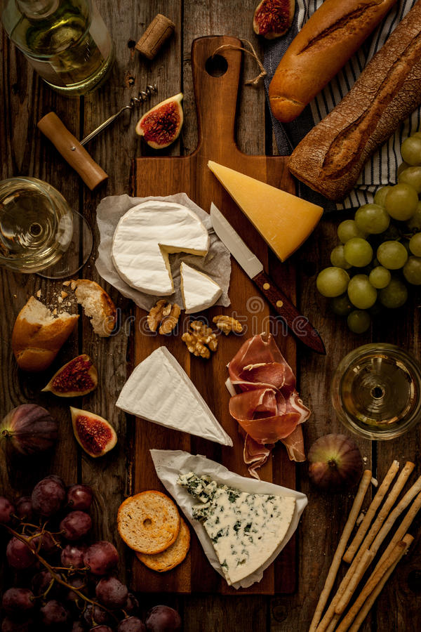 Different kinds of cheeses, wine, baguettes, fruits and snacks. On rustic wooden table from above. French tasting party or feast scenery. Dark moody artistic stock photo