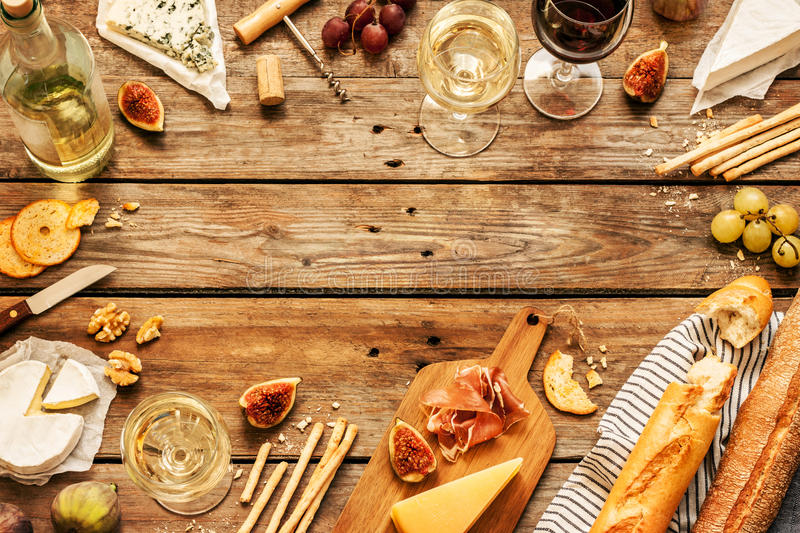 Different kinds of cheeses, wine, baguettes, fruits and snacks. On rustic wooden table from above. French tasting party or feast scenery. Background layout with royalty free stock images