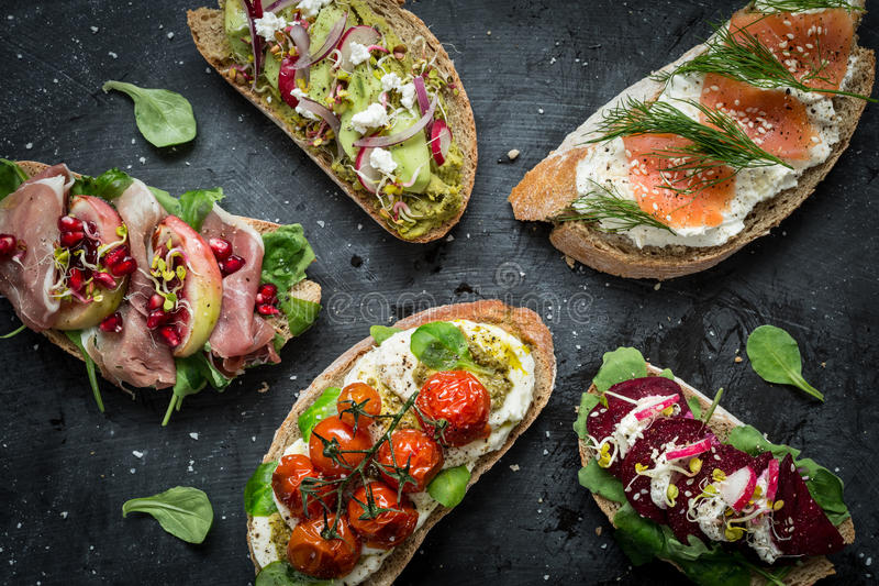 Different kinds of colorful sandwiches on black. Chalkboard background from above (top view). Party starter or appetizer - flat lay composition stock images