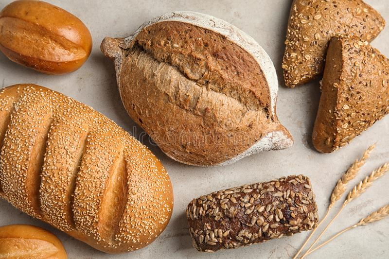 Different kinds of fresh bread. On grey table, flat lay royalty free stock photo