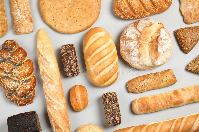Different kinds of fresh bread on light background. Flat lay stock photography