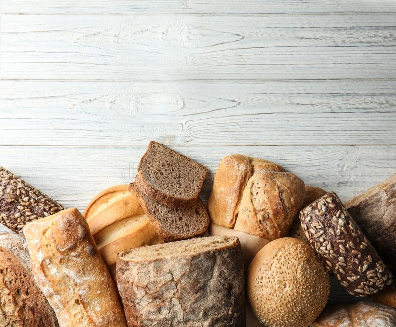 Different kinds of fresh bread on wooden table, flat lay. Space for text stock images